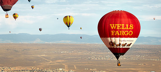 Several hot air balloons in the air against mountainous ground and blue sky. Focus is on the Wells Fargo balloon with logo, stagecoach, and text: Together we'll go far.